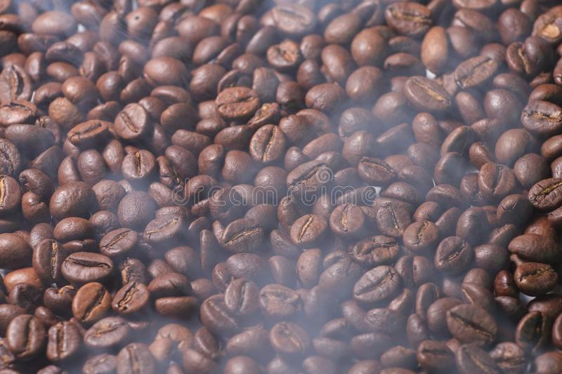 Black coffee beans texture with smoke of prepared hot coffee. Coffee beans texture with smoke of prepared hot coffee stock image