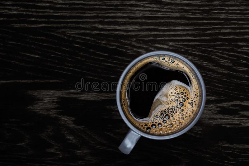 Black coffee in a blue-grey ceramic mug isolated on dark brown wood table with grain from above. Space for text stock photography