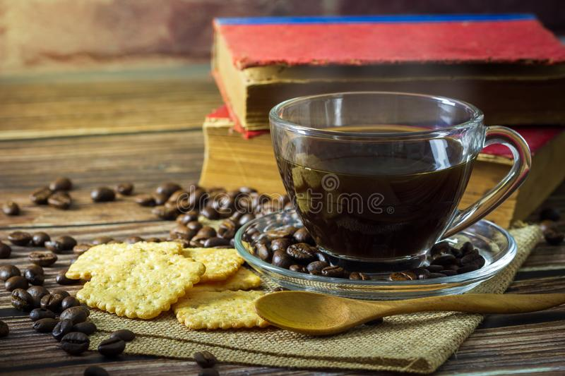 Black coffee in clear glass cup and coffee beans with crackers. royalty free stock photos