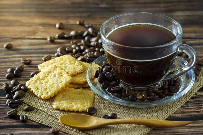 Black coffee in clear glass cup with coffee beans and crackers. stock photography