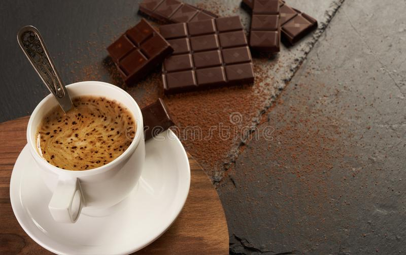 Black coffee with creamy foam, chocolate pieces and cocoa powder. Cup of coffee with broken chocolate pieces and cocoa powder on black stone background with copy stock photos