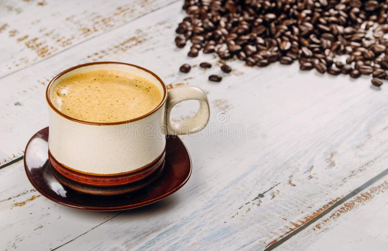 Black coffee cup and beans, on wooden table background royalty free stock photos
