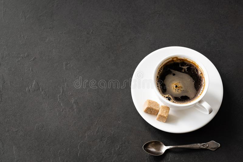 Black coffee cup with brown sugar on black concrete background royalty free stock photography