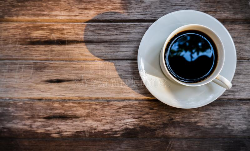 Black coffee cup with The morning sunlight  on old wooden background stock photos