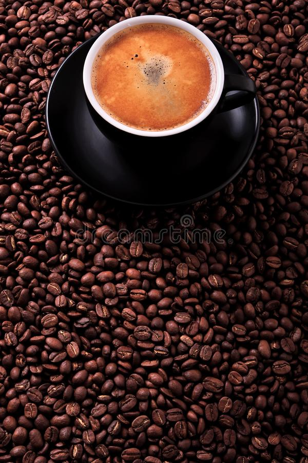 Black coffee cup with roasted beans background vertical copyspace royalty free stock photo