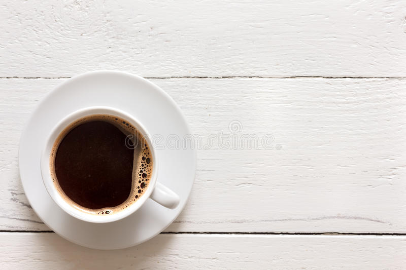 Black coffee in cup on rustic painted wood. From above. stock photo