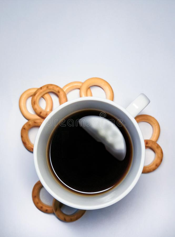 Black coffee in a cup and small bagels for breakfast on a white background royalty free stock photography
