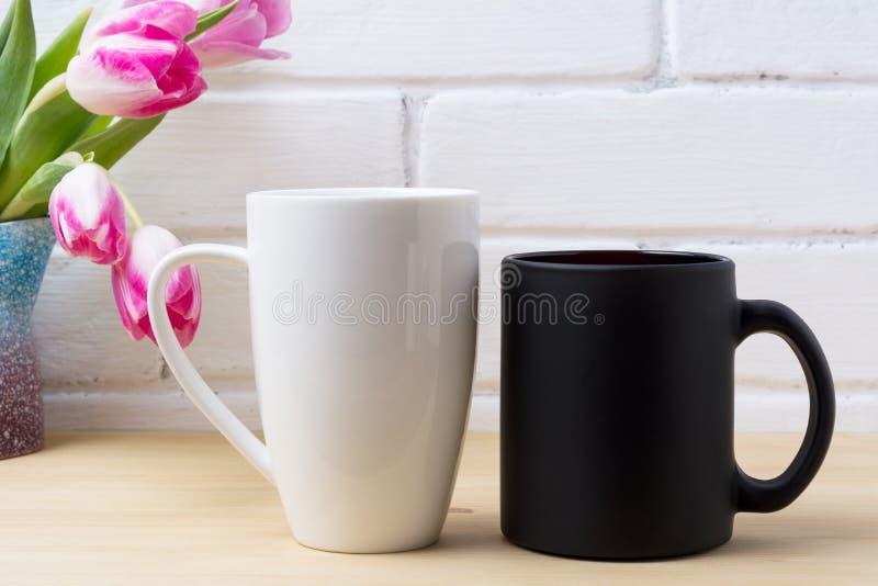 Black coffee cup and white cappuccino mug mockup with magenta tu stock image