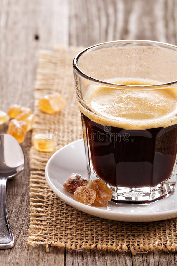 Black coffee in a glass. With crystal sugar royalty free stock photo