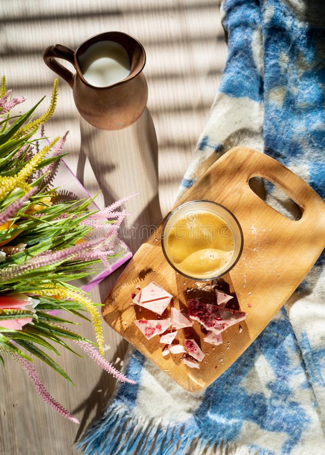 Black coffee in a glass cup, a milk jug, crushed pink chocolate on a blackboard and a bouquet of wildflowers stock photo