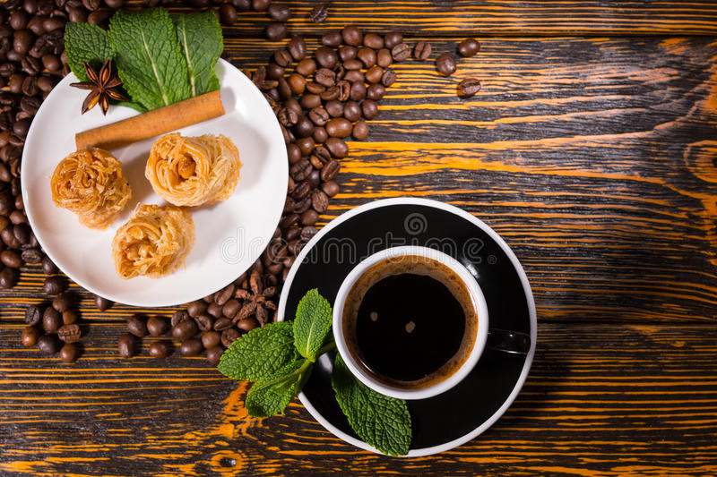 Black Coffee with Gourmet Pastries on Wood Table royalty free stock photos