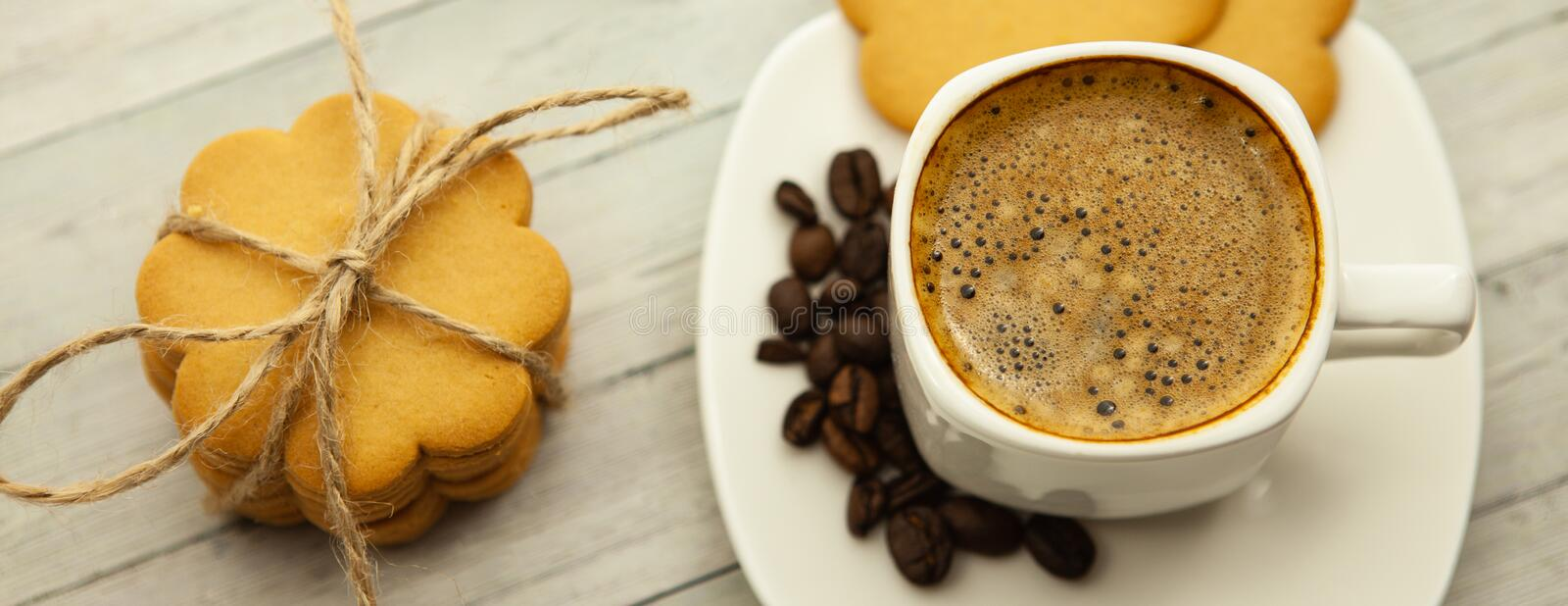 Black coffee with milk froth on a wooden background, ginger cookies and good mood in the morning, close-up royalty free stock photography