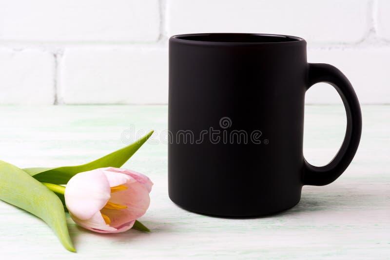 Black coffee mug mockup with pink tulip. Black coffee mug mockup with tender pink tulip flower. Empty mug mock up for brand promotion royalty free stock photography