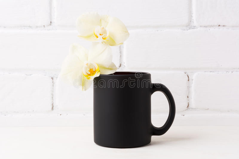 Black coffee mug mockup with soft yellow orchid. Empty mug mock up for brand promotion royalty free stock images