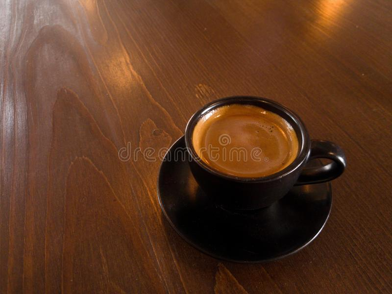 Black coffee mugs and spoon are placed on brown wood royalty free stock image