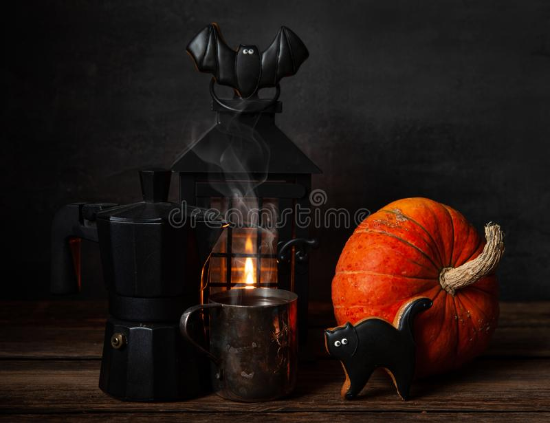 Black coffee pot, mug with black coffee, chocolate gingerbread, black lantern with  candle and pumpkin. Halloween concept,. Black coffee pot, mug with black royalty free stock images
