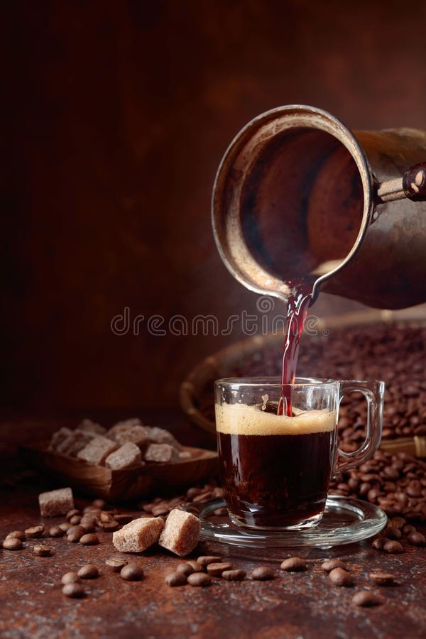 Black coffee is poured into a small glass cup from a copper coffee maker. Coffee beans and brown sugar pieces on a old table. Copy stock image