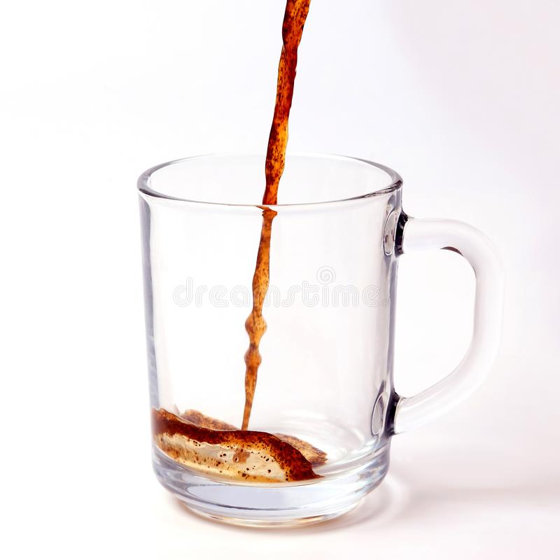 Black coffee is poured in a transparent mug on a white background stock images