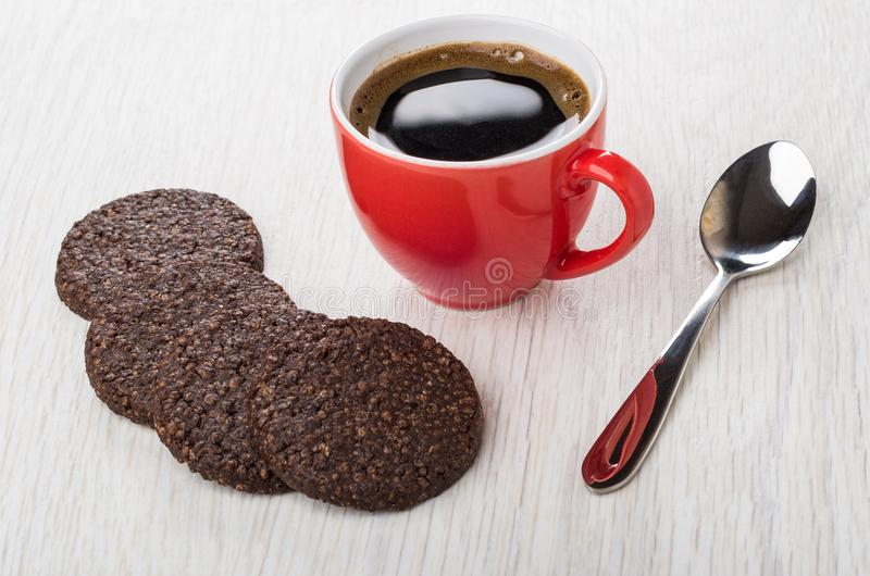 Black coffee in red cup, chocolate cookies with airy rice. Spoon on wooden table stock photography