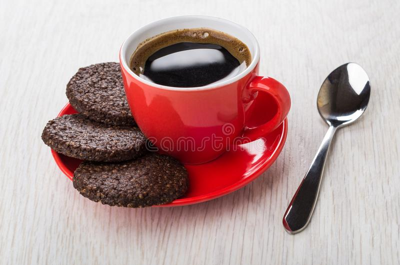 Black coffee, chocolate cookies with airy rice on saucer, spoon. Black coffee in red cup, chocolate cookies with airy rice on saucer, spoon on wooden table stock photos