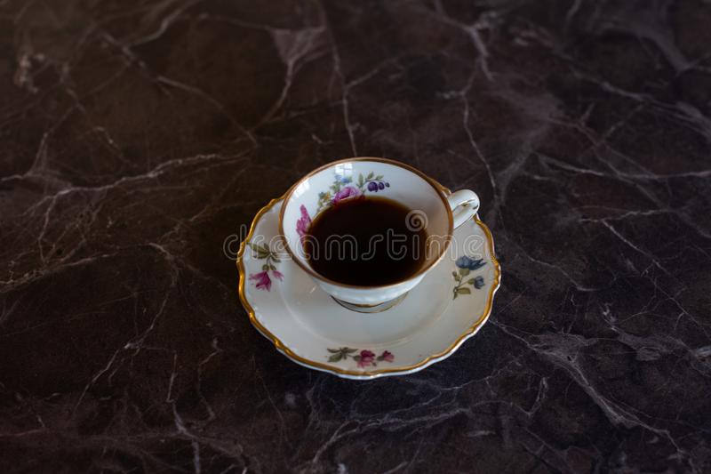 Black coffee served in an elegant, old china. royalty free stock image