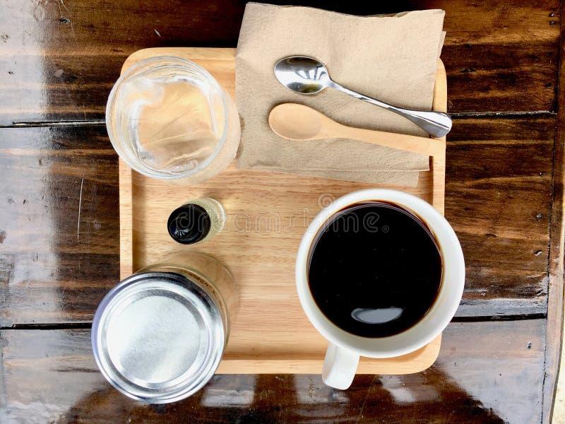 Black coffee with tea spoon, water on wood table. Black coffee and tea spoon, water on wood table stock photos