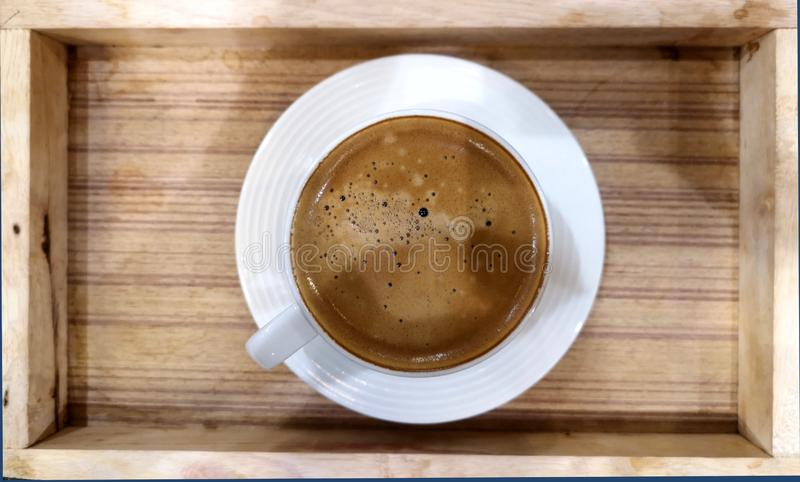Black coffee in a white ceramic mug. Placed in a wooden tray royalty free stock image