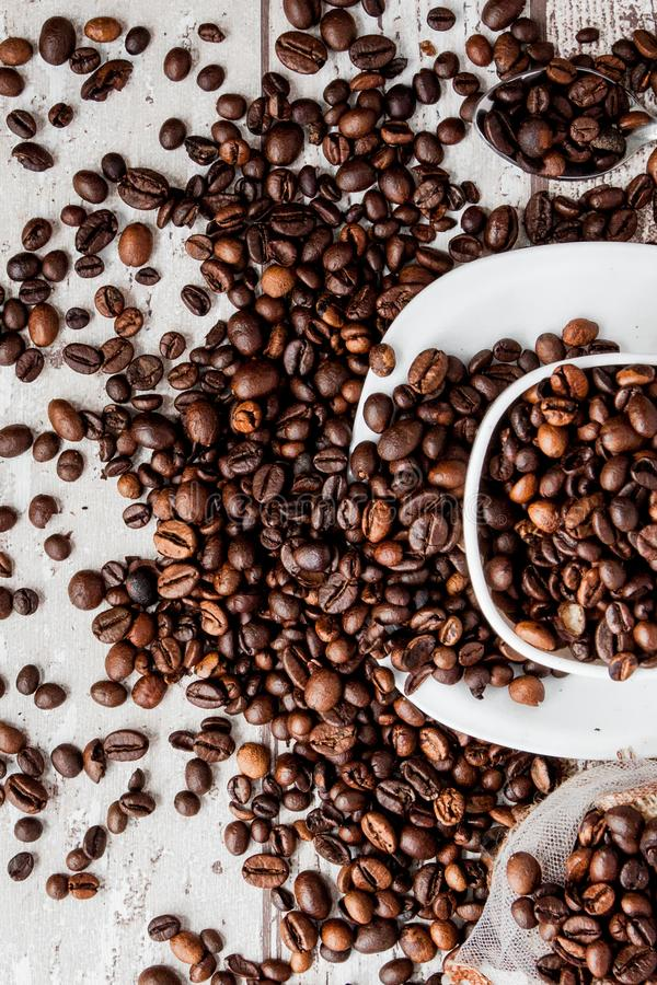 Black coffee in white cup and coffee beans on light wooden background. Top view, space for text stock photography