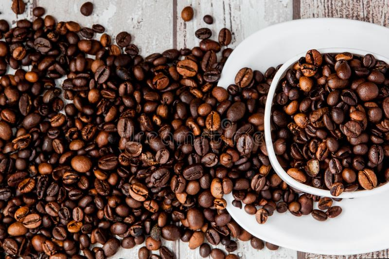 Black coffee in white cup and coffee beans on light wooden background. Top view, space for text royalty free stock images
