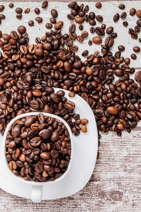 Black coffee in white cup and coffee beans on light wooden background. Top view, space for text stock image
