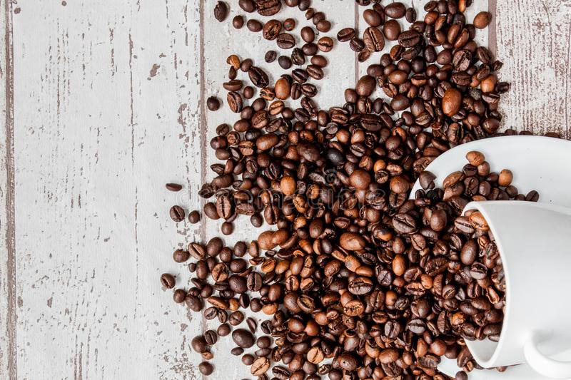 Black coffee in white cup and coffee beans on light wooden background. Top view, space for text stock photo