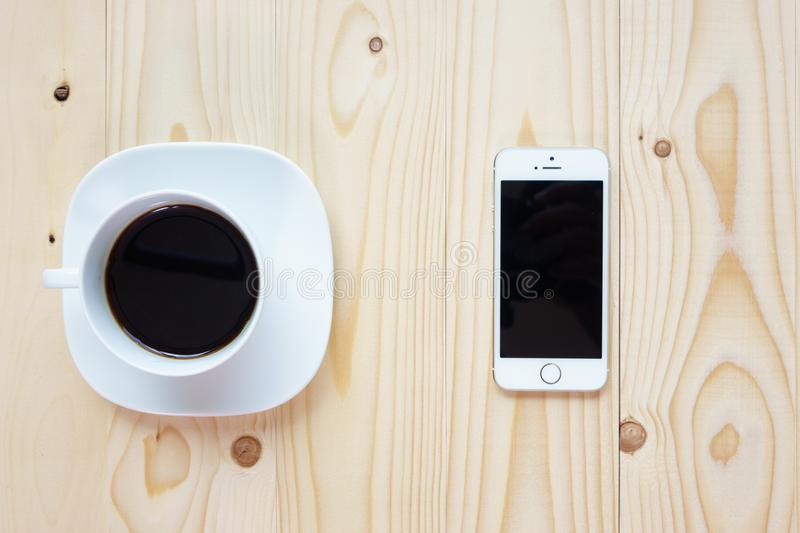 Black coffee and smartphone on wood background royalty free stock image