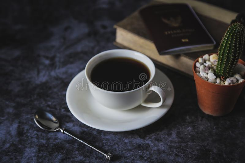 Black coffee in a white coffee cup and cactus placed on a black background stock photos