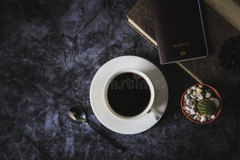 Black coffee in a white coffee cup and cactus placed on a black background stock image
