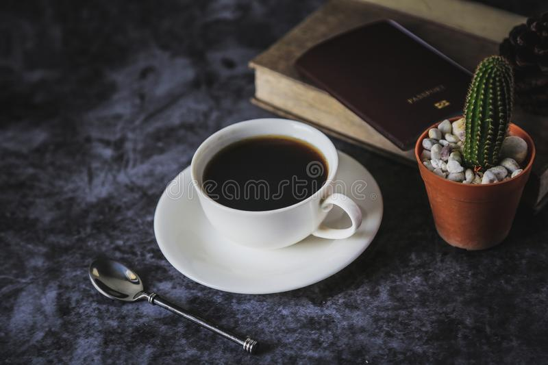 Black coffee in a white coffee cup and cactus placed on a black background stock photography