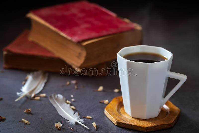 Black coffee in white cup and old books with feather and dried flower petals. stock image