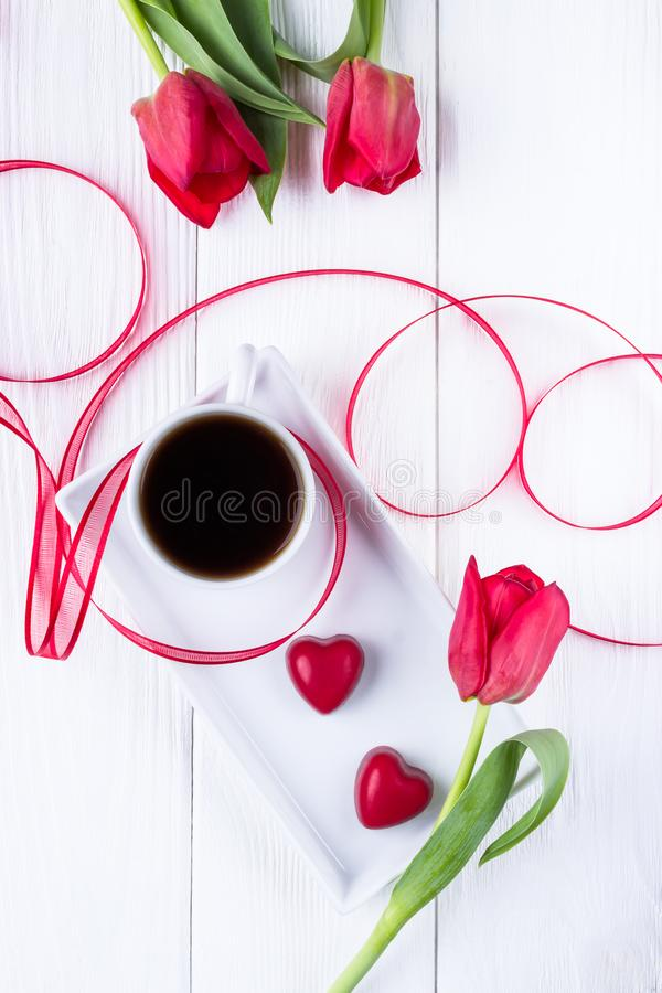Black coffee in a white cup, red tulips and two red hearts candy on a white wooden background. Top view. Happy Valentine`s Day. royalty free stock images