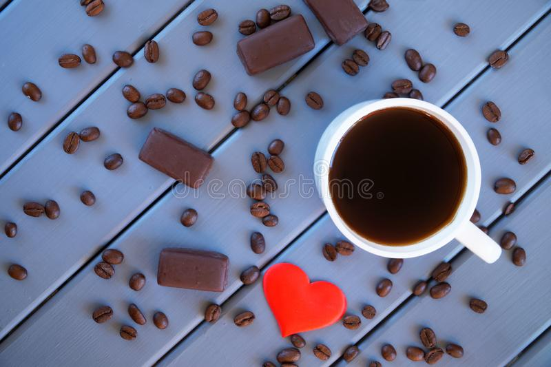 Black coffee in a white mug and chocolate candies on a table of painted wooden boards. stock image