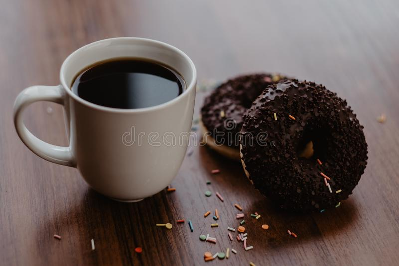 Black coffee in a white mug and two chocolate donuts on a wooden table by the window royalty free stock photos