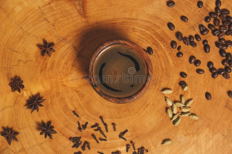 Black coffee in wooden cup on wooden background with different spices. Close-up espresso in brown cup, author processing royalty free stock photos