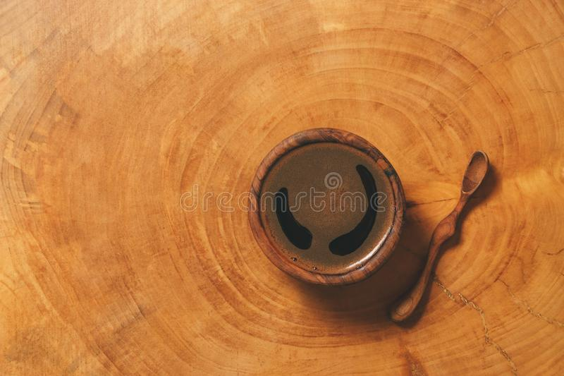 Black coffee in wooden cup with wooden spoon on background of wood. royalty free stock image