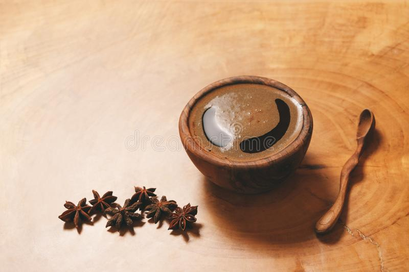 Black coffee in wooden cup with wooden spoon and star anise on wooden background. Copy-space and author processing. royalty free stock image