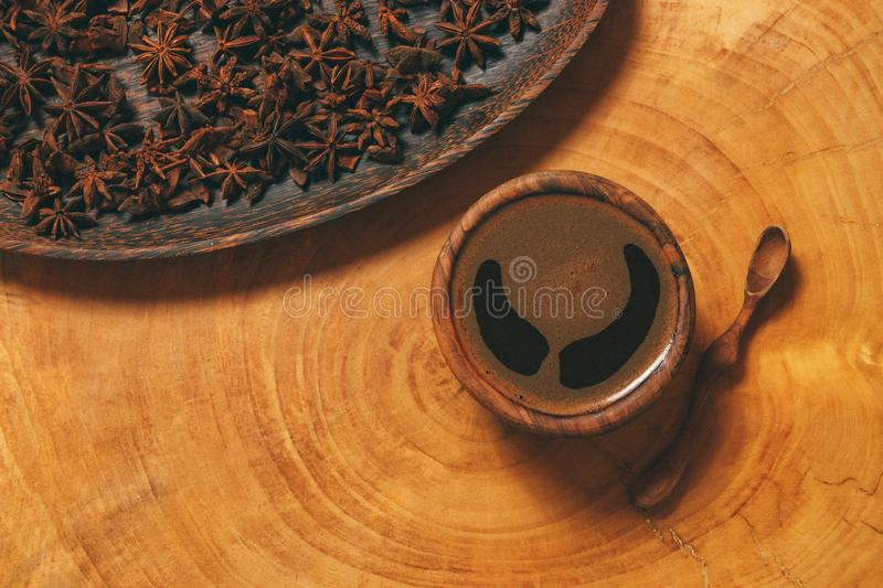 Black coffee in wooden cup with wooden spoon and star anise in a plate on wooden background. royalty free stock photo