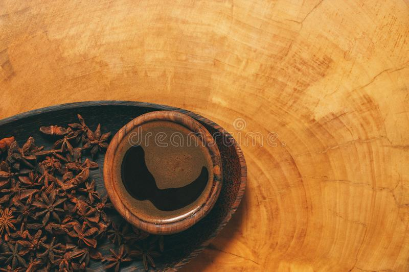 Black coffee in wooden cup with star anise in a plate on wooden background. Cpoy-space and author processing. royalty free stock image