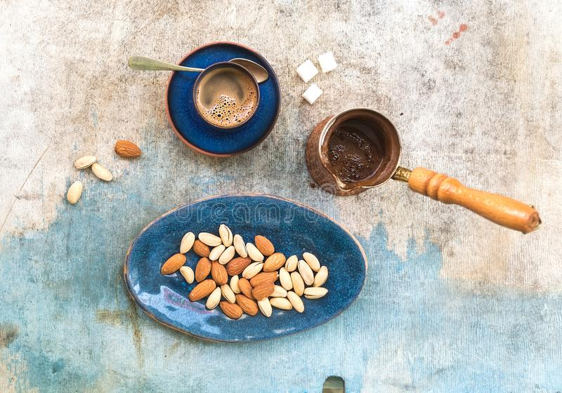 Black coffeee with almonds and pistachios. Over light blue backdrop. Top view royalty free stock photo