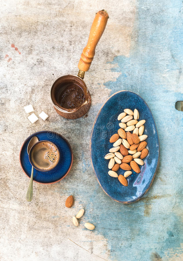 Black coffeee with almonds and pistachios over. Pld light blue backdrop. Top view royalty free stock images