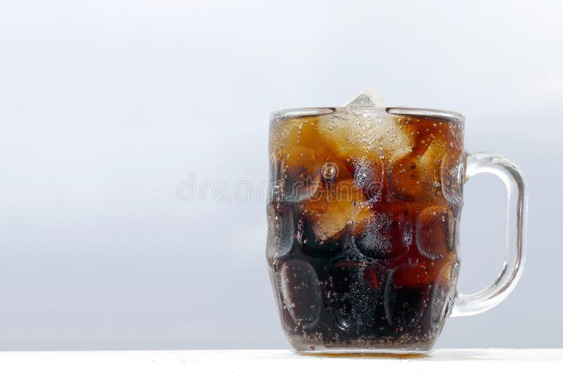 Black cola soda in glass with ice cubes for refreshments feel, beverage cola and cubes ice refreshing cool in glass on grey royalty free stock images