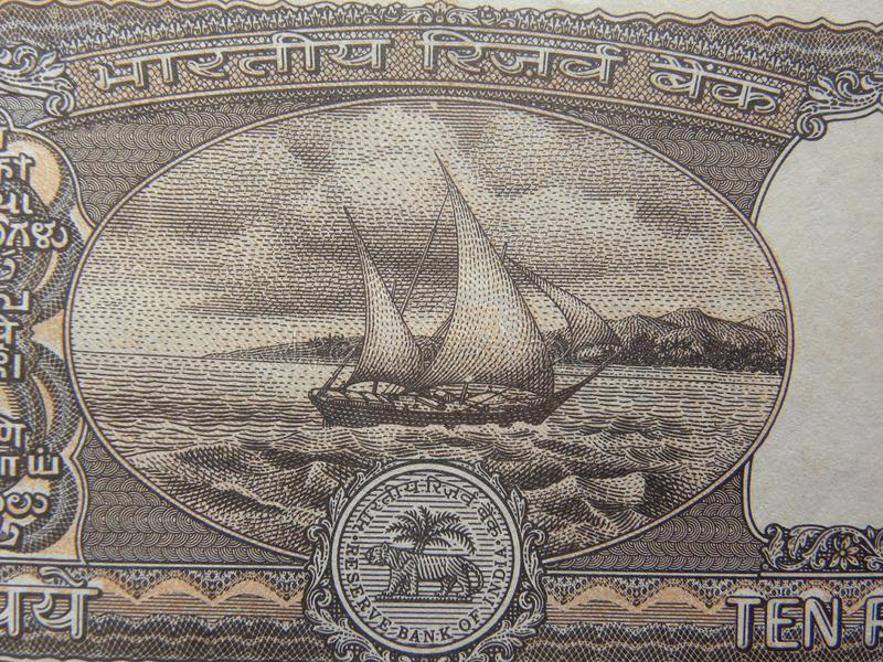 Boat in ocean portrait. Black color Boat in ocean portrait on old 10 rupees India banknote stock photography