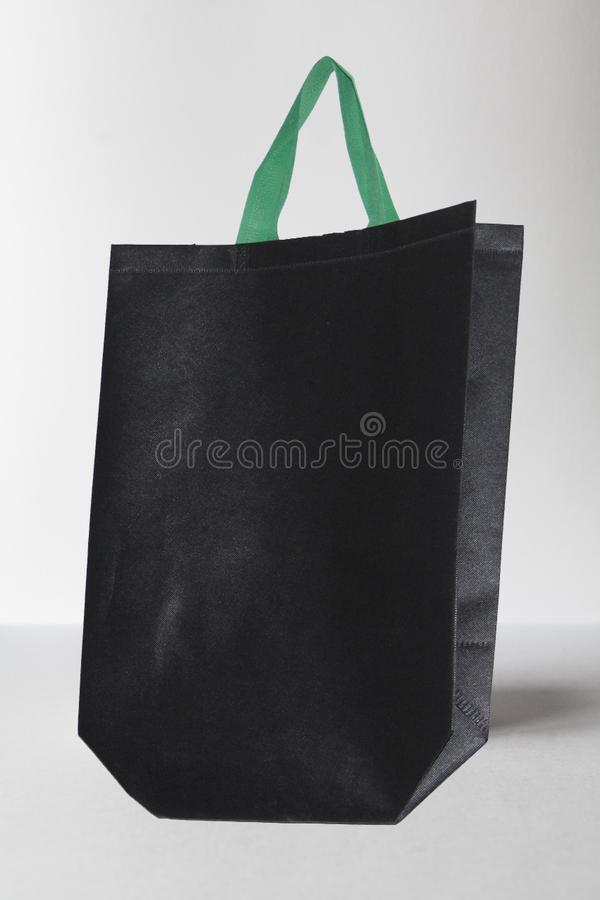 Black Color Eco friendly Reusable Bag with Green Handle on White background. Black Color Eco-friendly Reusable Bag with Green Handle Non Woven Bag, background royalty free stock photography