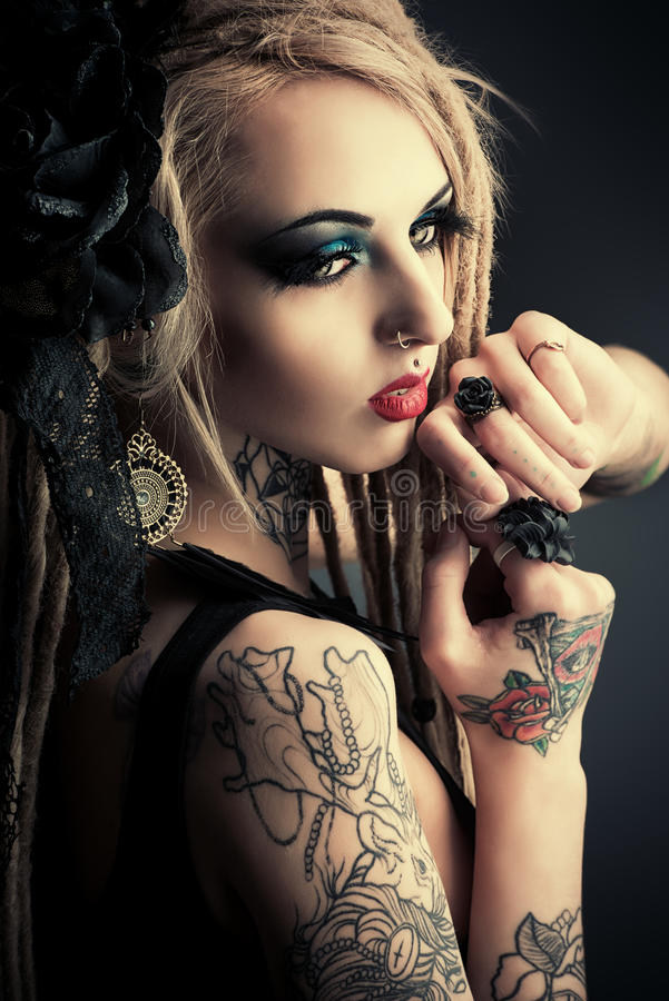 Black color. Gorgeous girl with black make-up and long dreadlocks. Gothic style. Fashion. Cosmetics, hairstyle. Tattoo royalty free stock photo